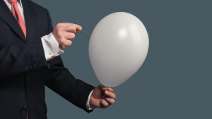 Businessman in Suit lets a Balloon burst with a needle